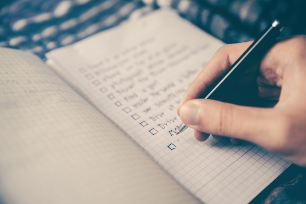 Person writing to-do list in notebook